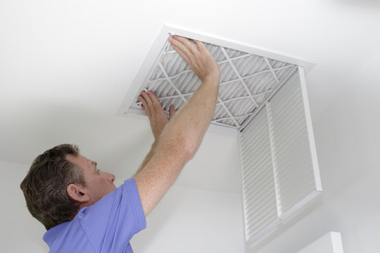 New Air Filter in Ceiling Male pushing a clean air filter into place in the ceiling with both hands. One fresh furnace air filter being secured in the intake grid of the white home ceiling.