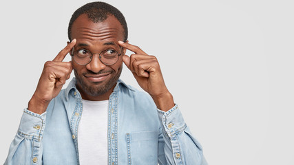 Photo of doubtful cheerful dark skinned guy keeps fingers on temples, looks with hesitation and tries to recollect something in mind, poses against white background with copy space for your text
