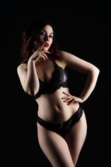 Beautiful sexy woman in lingerie posing on black studio background, low key studio shot