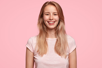 Wall Mural - Studio shot of pleasant looking young female with charming smile, being delighted to see something wonderful or meet with close friend, dressed in casual outfit, stands against pink background