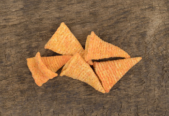 Top view of a portion of cheese flavored cone shaped corn chips on an old board.