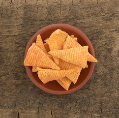 Top view of cheese flavored cone shaped corn chips in a bowl atop an old wood board.