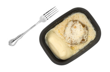 Fried beef steak with gravy TV dinner with a fork to the side.