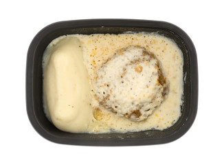 Fried beef steak with gravy TV dinner in a tray top view.