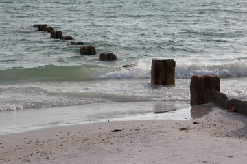 Rolling beach waves crashing into the shoreline with brick remnants in the water