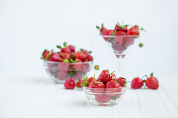 Fresh strawberries in a bowl on a white background.