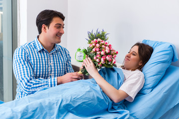 Caring loving husband visiting pregnant wife in hospital