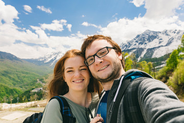 Travelling young couple take the selfie shot, smiling and happy. Summer mountains walk