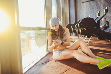 Theme sports, health and technology. beautiful sexy Caucasian woman sportswoman in gray sportswear and hat sits by window with sun setting uses smartphone listen music in large headphones on head