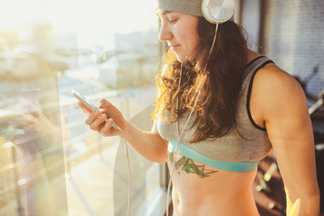 Theme sports, health and technology. beautiful sexy caucasian woman sportswoman in gray sportswear and hat standing by window with sun using martphone listen music in big white headphones on her head