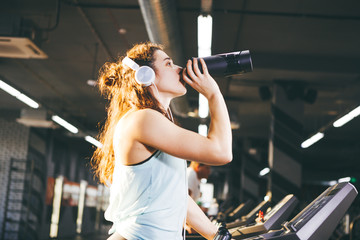 Sports nutrition and exercise. A beautiful young woman drinks protein from a bottle, a black shaker in the gym running on a treadmill, at the hands of a sports watch, in sunny weather.