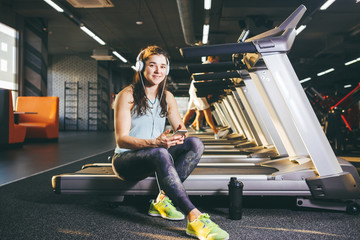 Beautiful young Caucasian girl sportswoman sitting, resting after training on treadmill against the backdrop of gym in sunny weather. Listens to music in sick white headphones, in hand holds the phone