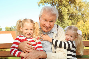 Elderly man with granddaughters in park