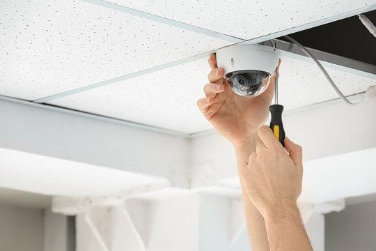 Technician installing CCTV camera on ceiling indoors, closeup