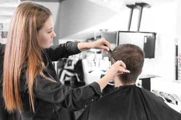 Female hairdresser cutting client's hair in salon