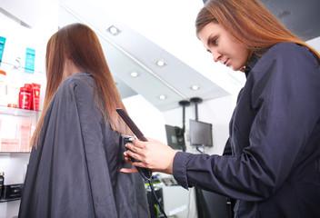 Professional stylist cutting woman's hair in salon