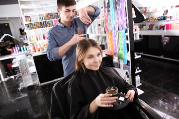 Male hairdresser cutting client's hair in salon