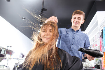 Professional stylist blow drying woman's hair in salon