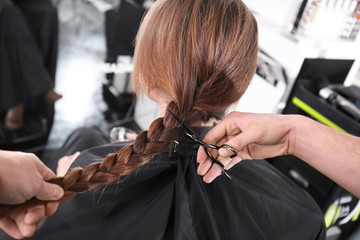 Professional stylist cutting off woman's braid in salon