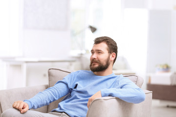 Portrait of confident mature man in armchair
