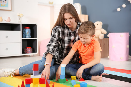 Young woman and little boy with autistic disorder playing at home