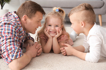 Cute little children and their father lying on cozy carpet at home