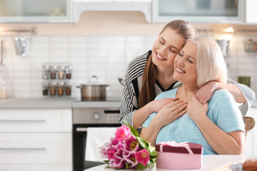 Daughter congratulating happy mature woman on Mother's Day at home
