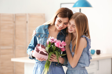 Teenage daughter congratulating happy woman on Mother's Day at home
