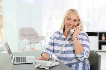Mature woman talking on phone at workplace