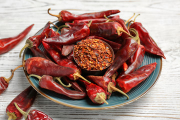 Plate with dry chili peppers and powder on wooden background