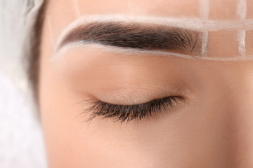 Young woman with marks on face before eyebrow permanent makeup procedure, closeup