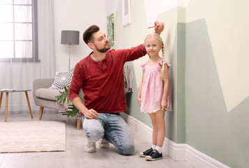 Young man measuring his daughter's height at home