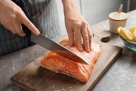 Woman cutting raw salmon fillet on wooden board