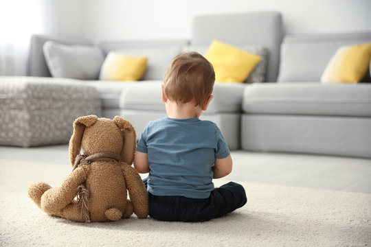 Little boy with toy sitting on floor in living room. Autism concept