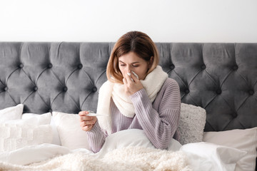 Sick woman with tissue and thermometer suffering from cold in bed