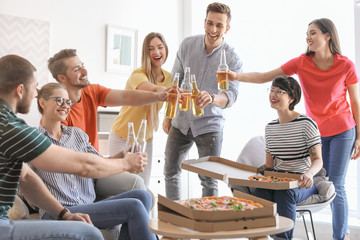 Young people having fun party with delicious pizza indoors