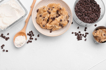 Flat lay composition with cookie dough, chocolate chips and flour on light background