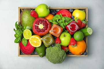 Crate with healthy detox smoothies and ingredients on light background, top view