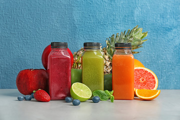 Bottles with healthy detox smoothies and ingredients on table