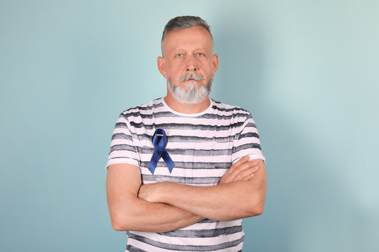 Mature man with blue ribbon on color background. Urological cancer awareness