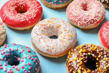 Delicious glazed doughnuts with sprinkles on color background