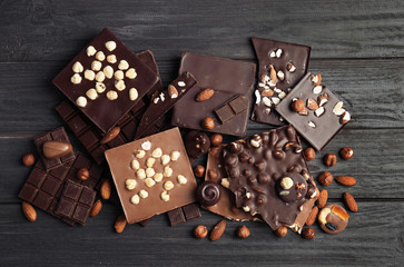 Different delicious chocolate bars and candies on wooden table, top view