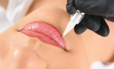 Young woman getting permanent makeup on lips in beautician salon, closeup