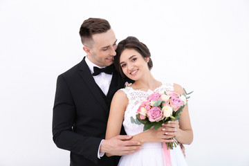 Young handsome groom and beautiful bride with bouquet on white background