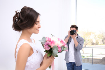 Professional photographer taking photo of wedding couple in studio