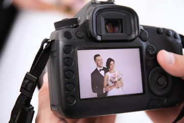 Professional photographer holding camera with lovely wedding couple on display, closeup