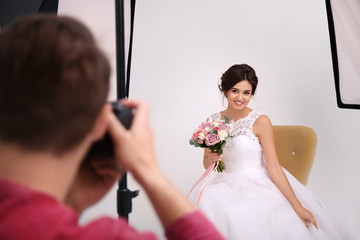 Professional photographer taking photo of beautiful bride in studio