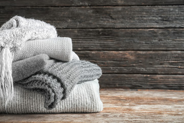 Fototapete - Pile of warm knitted clothes on table