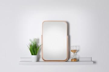 Shelf with modern mirror on white wall
