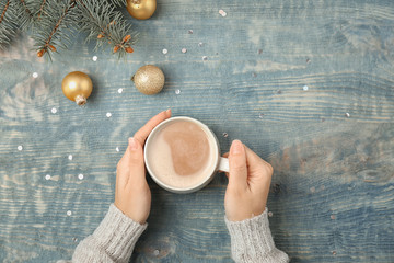 Woman with delicious hot cocoa drink at table, top view